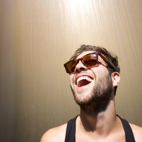 Close up portrait of a cheerful young man laughing with sunglasses