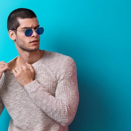 Brutal man portrait wearing sunglasses on blue studio background. Sensual male wearing sweater and jeans, ready to take off his pullover